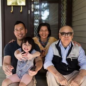 Asian family sitting with grandfather on the porch of their home